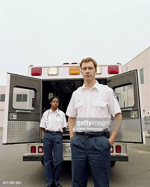 Paramedics standing at rear of ambulance