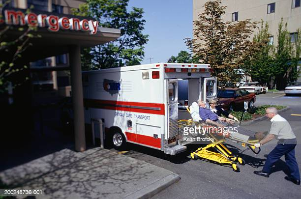 Paramedics taking patient on gurney from ambulance at emergency ward