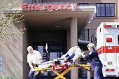 Paramedics taking patient on gurney into emergency ward at hospital
