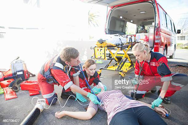 Paramedics tending patient lying on road