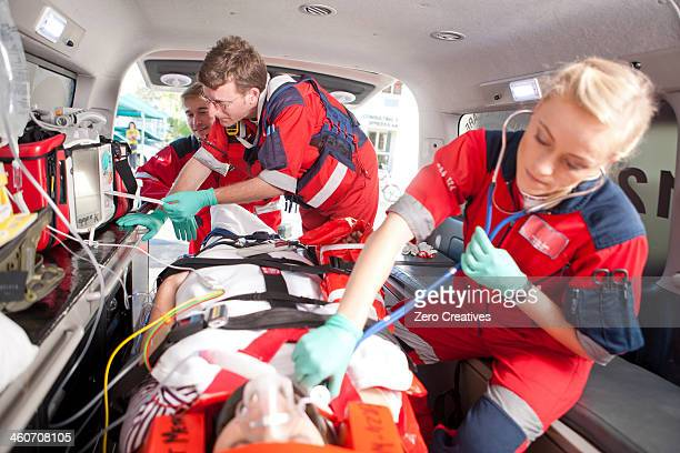 Paramedics using stethoscope on patient in ambulance