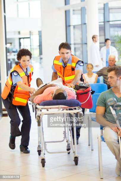 Paramedics wheeling patient in hospital