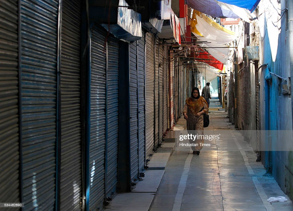 A woman walk past closed shops during a strike called by separatists against creation of the separate clusters for the Pandits and establishing of Sainik colonies on May 26, 2016 in Srinagar, India.