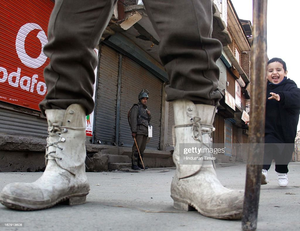 Paramilatary soldiers stand guard as Kashmiri child walks during a strike, on March 1, 2013 in Srinagar, India. As Kashmir valley observed a strike called by separatists in support of their demand for return of mortal remains of Parliament attack convict Afzal Guru .