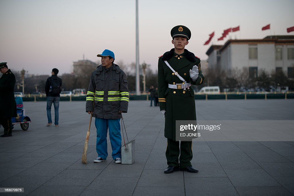 A paramilitary guard gestures as he stands next to a street sweeper prior to the daily flag-lowering ceremony on Tiananmen Square in Beijing on March 4, 2013. Thousands of delegates from across China meet this week to seal a power transfer to new leaders whose first months running the Communist Party have pumped up expectations with a deluge of propaganda. AFP PHOTO / Ed Jones