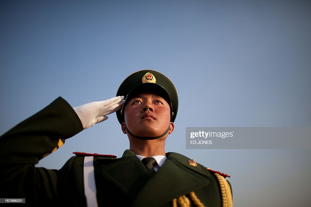 A paramilitary guard salutes during the opening session of the Chinese People's Political Consultative Conference (CPPCC) at the Great Hall of the People in Beijing on March 3, 2013. Thousands of delegates from across China meet this week to seal a power transfer to new leaders whose first months running the Communist Party have pumped up expectations with a deluge of propaganda. AFP PHOTO / Ed Jones
