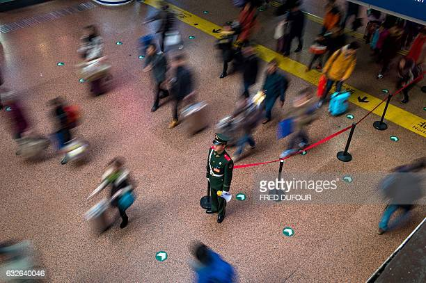 TOPSHOT A paramilitary guard stands as passengers arrive at Beijing West Railway Station to travel back to their hometowns for the 'Spring Festival'...