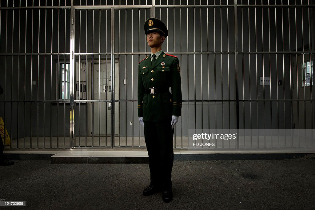 A paramilitary guard stands before the bars of a main gate to the No.1 Detention Center during a government guided tour in Beijing on October 25, 2012. The rare visit to the facility, which has capacity for 1,000 inmates, was opened to the foreign media as Beijing prepares for the 18th Congress of the Communist Party of China. AFP PHOTO / Ed Jones