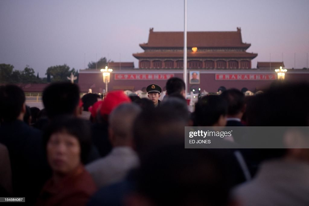 A paramilitary guard (C) stands on Tiananmen Square as tourists arrive to watch the daily flag-raising ceremony early on October 23, 2012. Supporters of disgraced politician Bo Xilai have published a letter on a leftist website urging him not to be expelled from China's parliament which would pave the way for him to face trial over alleged corruption and charges. AFP PHOTO / Ed Jones