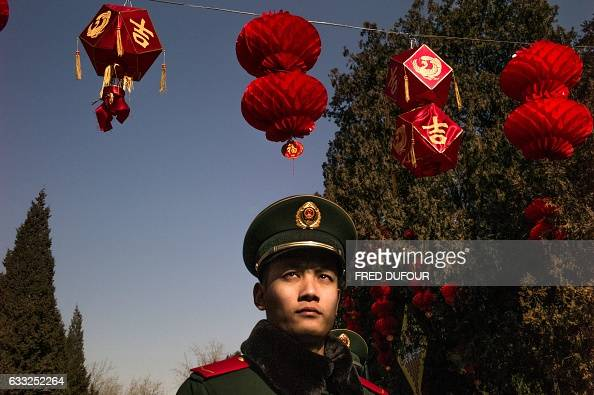 TOPSHOT A paramilitary guard walks under red lanterns at a temple fair in Ditan park during Lunar New Year celebrations in Beijing on February 1 2017...