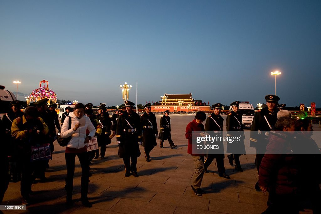 Paramilitary guards escort tourists from Tiananmen Square after the daily flag-lowering ceremony in Beijing on November 11, 2012. The week-long Communist Party Congress, held every five years, will end with a transition of power to Vice President Xi Jinping, who will govern for the coming decade amid growing pressure for reform of the communist regime's iron-clad grip on power. AFP PHOTO / Ed Jones