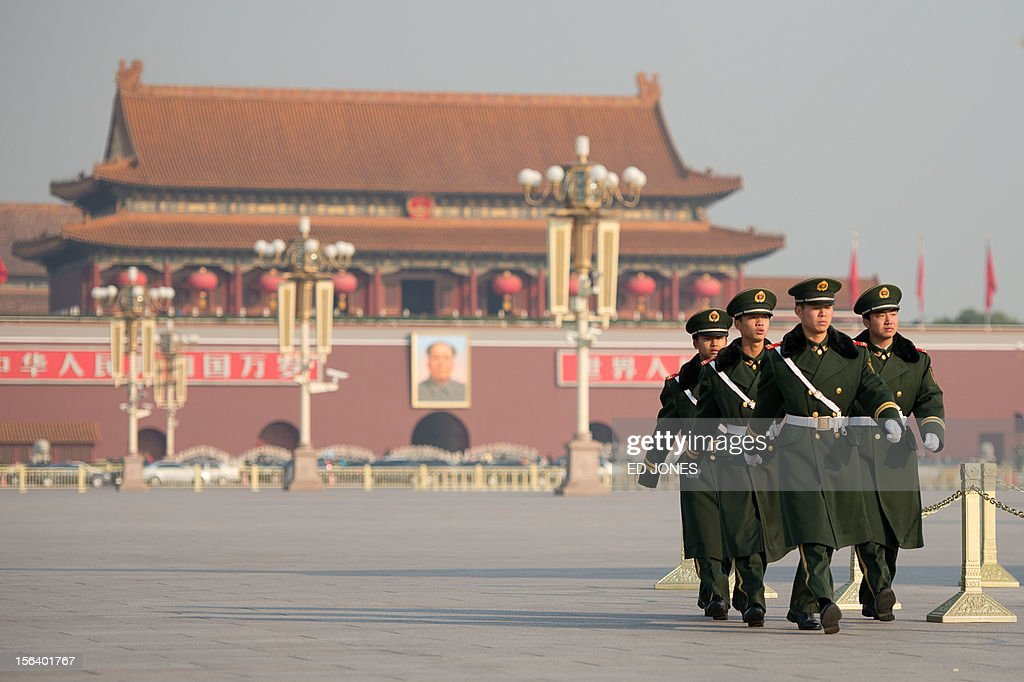Paramilitary guards walk on a closed-off Tiananmen Sqaure, near the Great Hall of the People prior to the unveiling of a new Politburo Standing Committee, in Beijing on November 15, 2012. Xi Jinping is set to take the reins of China's all-powerful Communist Party in a leadership transition that will put him in charge of the world's number two economy for the next decade. AFP PHOTO / Ed Jones