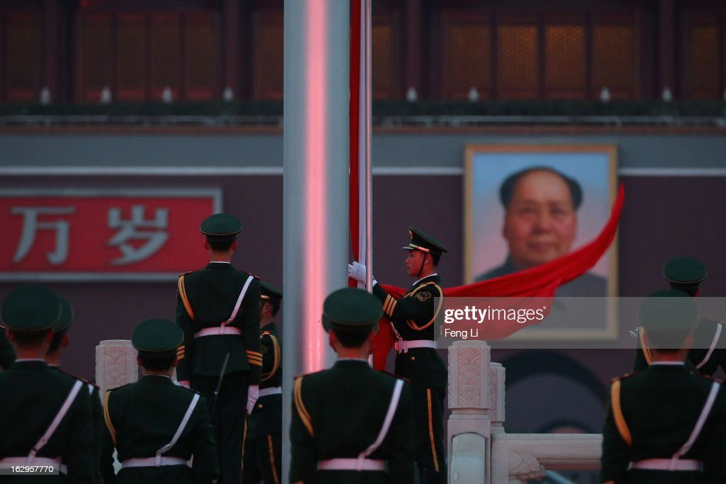 A paramilitary police officer collects the Chinese national flag during the flag-lowering ceremony in front of a giant portrait of the late chairman Mao Zedong at Beijing's Tiananmen Square on March 2, 2013 in Beijing, China. The reshuffle will be completed at the first annual session of the 12th National People's Congress (NPC), which is scheduled to begin on March 5, and the first annual session of the 12th National Committee of the Chinese People's Political Consultative Conference (CPPCC), which will commence on March 3.