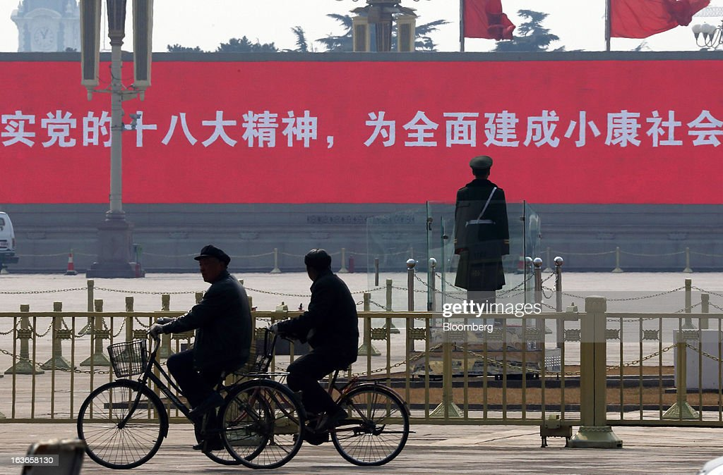 A paramilitary police officer, right, stands guard as people cycle past at Tiananmen Gate in Beijing, China, on Thursday, March 14, 2013. Xi Jinping was named China's president by the national legislature, replacing Hu Jintao in the country's most rapid formal transfer of power in more than a generation. Photographer: Tomohiro Ohsumi/Bloomberg via Getty Images