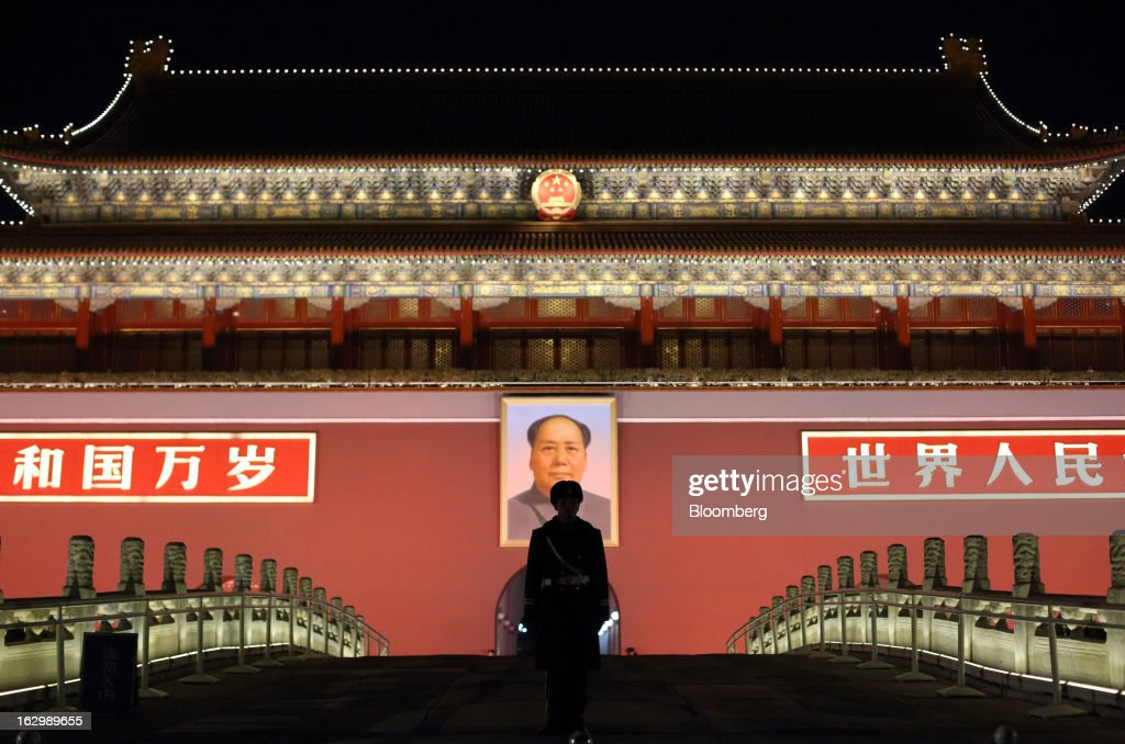 A paramilitary police officer stands guard in front of a portrait of former Chinese leader Mao Zedong at Tiananmen Gate at night in Beijing, China, on Saturday, March 2, 2013. Premier Wen Jiabao will this week formally announce this year's economic targets when he delivers his final work report to the National People's Congress, which begins on March 5. Photographer: Tomohiro Ohsumi/Bloomberg via Getty Images