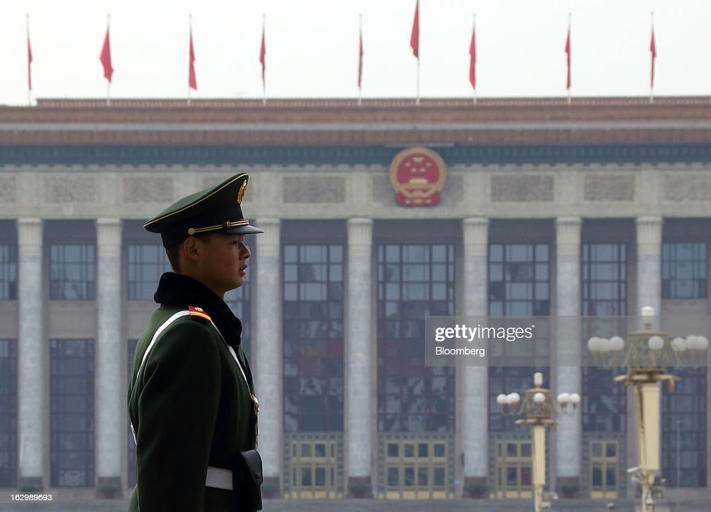 A paramilitary police officer stands guard in front of the Great Hall of the People in Beijing, China, on Saturday, March 2, 2013. Premier Wen Jiabao will this week formally announce this year's economic targets when he delivers his final work report to the National People's Congress, which begins on March 5. Photographer: Tomohiro Ohsumi/Bloomberg via Getty Images