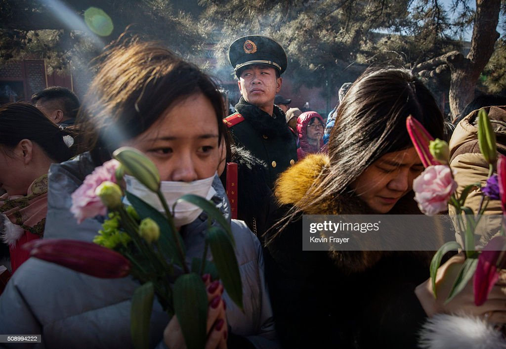 A Paramilitary police officer watches over Chinese worshippers as they pray at the Yongchegong Lama Temple on February 8, 2016 in Beijing, China. The Chinese Lunar New Year also known as the Spring Festival, which is based on the Lunisolar Chinese calendar, is celebrated from the first day of the first month of the lunar year and ends with Lantern Festival on the fifteenth day.