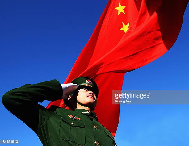 Paramilitary policeman does a national flag rising ceremony to mark the New Year before thousands of people climb the Great Wall on January 1 2009 in...