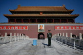 A paramilitary policeman stands before a portrait of Mao Zedong at Tiananmen Gate and the Forbidden City in Beijing on October 29 2013 A fatal car...