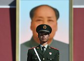A paramilitary policeman stands guard in front of the portrait of late communist leader Mao Zedong on Tiananmen Gate in Beijing on China's National...