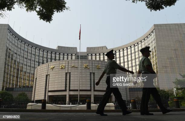 Paramilitary policemen patrol in front of the People's Bank of China the central bank of China in Beijing on July 8 2015 China stocks took another...