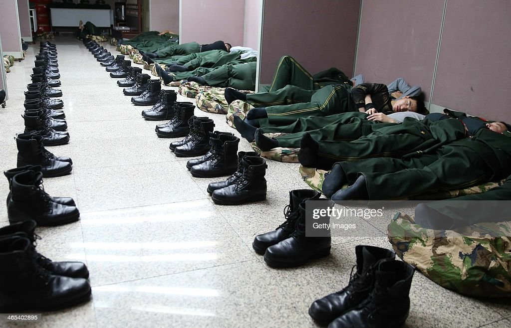 Paramilitary policemen sleep on the ground at Beijing West Railway Station on January 26, 2014 in Beijing, China. The Chinese Spring Festival travel rush began on January 16 and about 3.62 billion passenger trips are expected to be made across the country, with around 257 million train trips during the 40-day lunar New Year travel period.