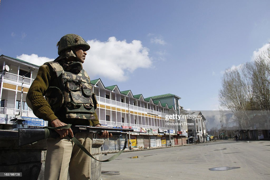 Paramilitary soldier stands guard during a curfew, on March 15, 2013 on Srinagar, India. Curfew continued for the second consecutive day in Srinagar district following the alleged firing by CRPF personnel on Wednesday in which a youth was killed. CRPF personnel allegedly opened fire after coming under attack by a group of stone pelters while on their way to hospital to donate blood for their colleagues injured in terror attack.