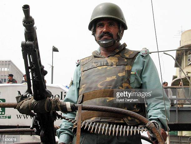 A paramilitary soldier stands guard following a deadly attack on a Christian welfare organization September 25 2002 in Karachi Pakistan According to...