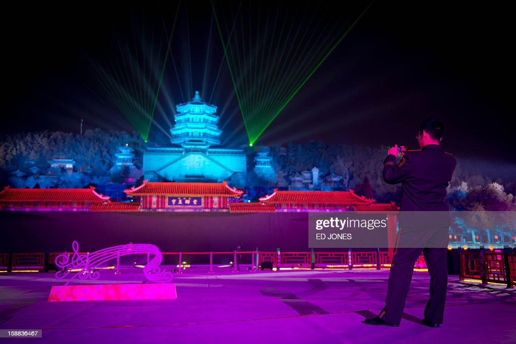 A paramilitary soldier takes a photo as a light show illuminates the Summer Palace prior to a new year count-down event in Beijing on December 31, 2012. AFP PHOTO / Ed Jones