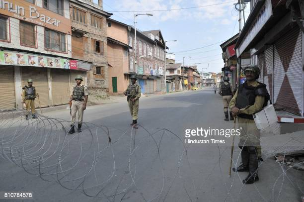 Paramilitary soldiers stand guard near barbed wire set up as barricade during curfew in Lal Chowk area on July 8 2017 in Srinagar India Authorities...