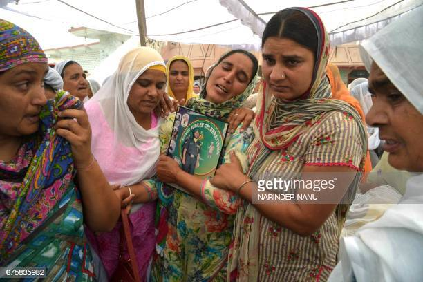 Paramjeet Kaur the mother of slain Indian Army soldier Paramjeet Singh is supported by relatives as she cries during his funeral ceremony at Vein...