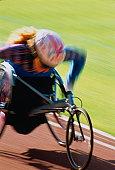 Paraplegic athlete using racing wheelchair (blurred motion)