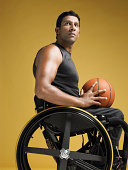 Side view of a confident paraplegic athlete in wheelchair holding basketball against yellow background