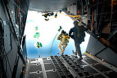 Pararescuemen perform a static-line jump out of a C-130 Hercules over water near Kadena Air Base, Japan.