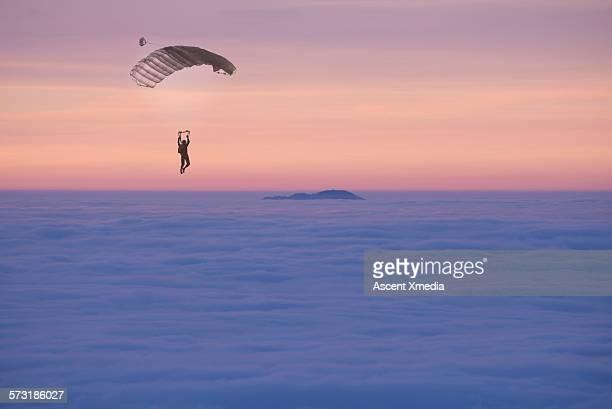 Parasailer descends through cloud layer to island