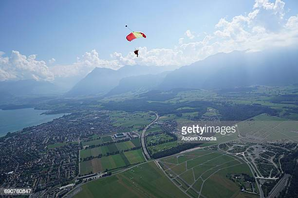 Parasailer glides above mountain landscape