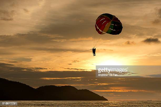Parasailing over the sea at sunset