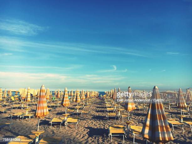 Parasol And Empty Lounge Chairs On Sand At Beach Against Sky