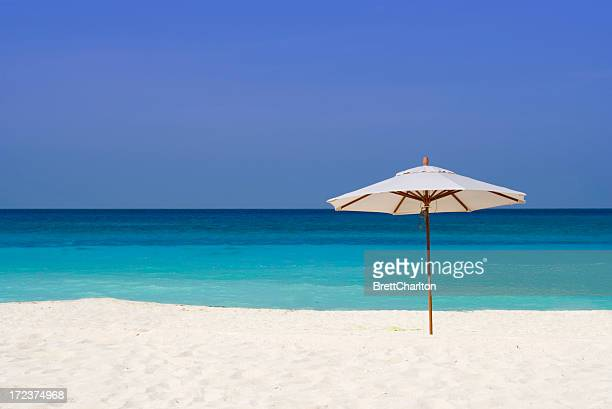 A parasol in the sand at a beach