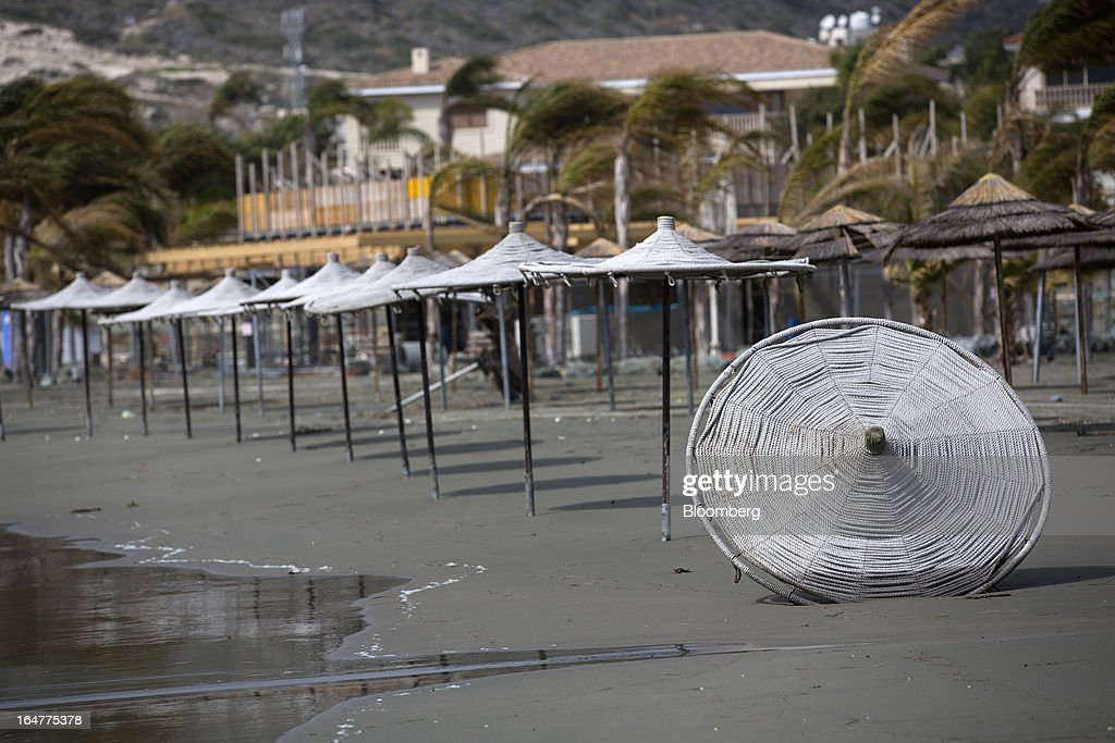 A parasol lies on an empty beach after being blown over in high winds in Limassol, Cyprus, on Wednesday, March 27, 2013. The ECB said on March 25 it won't stop the Cypriot central bank from providing the island's banking sector with emergency funding. Photographer: Simon Dawson/Bloomberg via Getty Images