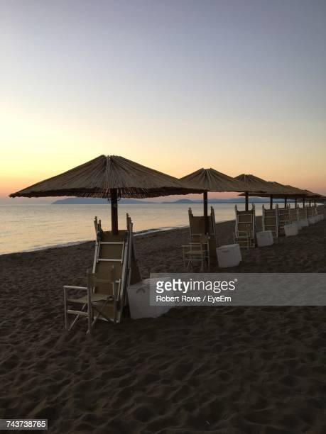 Parasols And Chairs Arranged At Beach Against Sky During Sunset