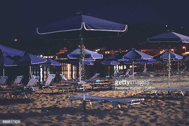 Parasols And Deck Chairs At Beach Against Sky