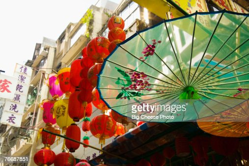 Parasols and lanterns hanging outside Hong Kong shop : Stock Photo