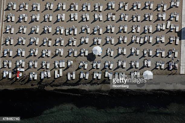 Parasols and loungers stand in line on a private beach on the outskirts of Athens Greece on Thursday June 25 2015 Greece could tap euroarea funds of...