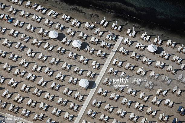 Parasols and sun loungers stand in line on a private beach on the outskirts of Athens Greece on Thursday June 25 2015 Greece could tap euroarea funds...