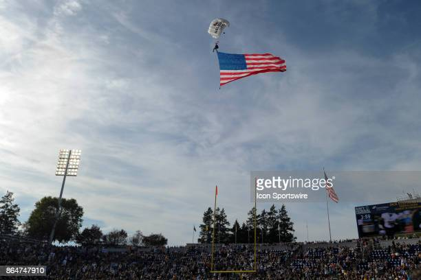 A paratrooper bring in an American Flag over Navy Marine Corps Memorial Stadium in Annapolis MD on October 21 2017