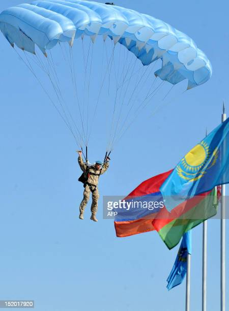 A paratrooper descends behind flags of the nations members of the Collective Security Treaty Organization during a ceremony marking the CSTO Rapid...