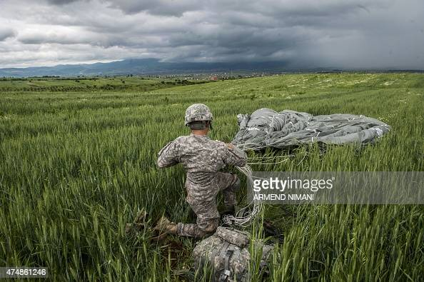A US paratrooper of the Army's 4th 25 Infantry Brigade Combat Team part of the NATOled peacekeeping mission in Kosovo packs his parachute during a...
