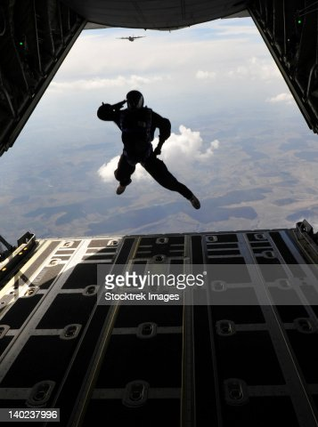 A paratrooper salutes as he jumps out of a C-130J Super Hercules. : Foto de stock