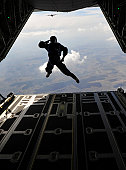 March 18, 2011 - A paratrooper salutes as he exits a C-130J Super Hercules during a combined high-altitude, low-open jump, over a landing zone near Campia Turzii, Romania. This jump was conducted as p